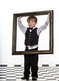 Freckled red-hair little boy with big picture frame. Royalty Free Stock Photography