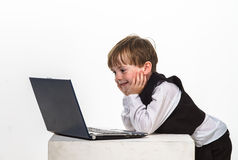 Freckled red-hair little boy with laptop. Royalty Free Stock Image