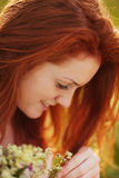 Freckled red-haired girl with a bouquet Royalty Free Stock Images