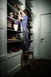 Freckled red-haired little boy searching book on bookcase Royalty Free Stock Image