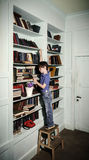 Freckled red-haired little boy searching book on bookcase Stock Photography