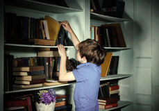 Freckled red-haired little boy searching book on bookcase Stock Photos