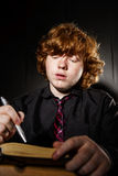 Freckled red-haired teenage boy reading book, education concept Stock Photos