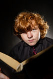 Freckled red-haired teenage boy reading book, education concept Royalty Free Stock Photography