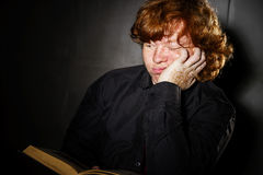 Freckled red-haired teenage boy reading book, education concept Royalty Free Stock Photo