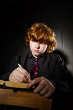 Freckled red-haired teenage boy reading book, education concept Stock Images