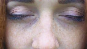 Freckled rode haarmeisje opent groene ogen, close-up, mooie vrouw met sproeten stock footage