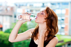 Freckled woman drinks water from bottle Stock Photography