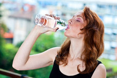 Freckled woman drinks water from bottle. Attractive red hair freckles woman drinks water from plastic bottle Stock Photography