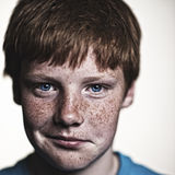Freckles. Redhead boy with freckles looking amused Royalty Free Stock Image