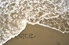 Fred som är skriftlig i sanden Arkivbild