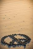 Fred undertecknar in sanden Arkivfoto