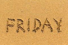 fredag - som är skriftlig vid handen på en guld- strandsand Abstrakt begrepp Arkivbilder