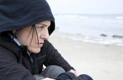 Freddo della donna sulla spiaggia Immagine Stock