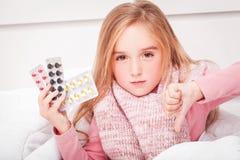Freddo ed influenza Una ragazza con le pillole in sue mani immagini stock