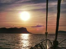 Fredom: Sailing with big sail, slow wind on the ocean towards a sunset at sea; give a sense of calm, relax, vacation and transport Royalty Free Stock Photo