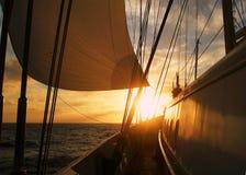 Fredom: Segla med stort segla, långsam vind på havet in mot en solnedgång på havet; ge en avkänning av stillhet, koppla av, semes Arkivbild