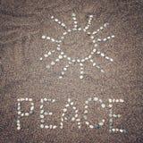 Fredord och solsymbol på sanden - tonat foto Arkivbild