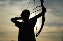 Robin Hood. Picture of a young archer in backlight that is going to throw the arrow Royalty Free Stock Images