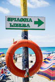Free beach, indicator sign on wooden post with  lifesaver Stock Photos