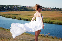Free bride standing above the river Stock Image