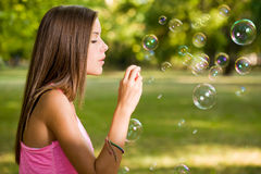 Free the bubbles. Free the bubbles, portrait of a beautiful young girl having fun outdoors blowing soap bubbles Stock Images