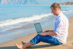 Free businessman working on  sandy beach Stock Photo