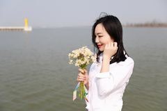 Free careless causual beauty enjoy good time next to a lake ocean river beach hold a bunch of flower. She is smile laugh happy woman, she is from Asian Chinese royalty free stock photography
