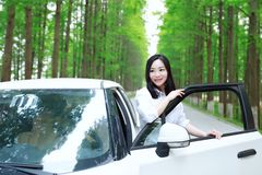 Free carelss happy woman enjoy cozy comfortable life drive a white car on a road in forest. Asian Chinese woman yoga by a lake, capped mountains on the Royalty Free Stock Images