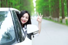 Free carelss happy woman enjoy cozy comfortable life drive a white car on a road in forest. Asian Chinese woman yoga by a lake, capped mountains on the Stock Images