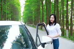 Free carelss happy woman enjoy cozy comfortable life drive a white car on a road in forest. Asian Chinese woman yoga by a lake, capped mountains on the Stock Photos