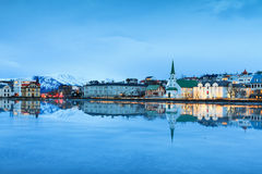 Free church cityscape. Beautiful reflection of the cityscape of Reykjavik and the Free church in lake Tjornin at the blue hour in winter royalty free stock photo