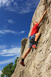Free Climber. A guy climbs on a rock against the blue sky Stock Image