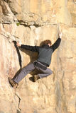 Free Climber. Traversing rock face at full stretch Royalty Free Stock Image