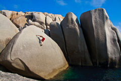 Free climber above the water. Free climber on a granite wall above the sea in Capo Testa, Sardinia, Italy Stock Photography