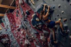 Free climber female bouldering indoors. Back view Stock Photo