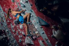 Free climber female bouldering indoors. Back view Royalty Free Stock Photo
