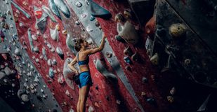 Free climber female bouldering indoors. Back view Stock Photos