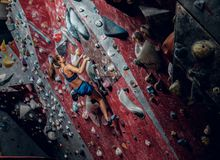 Free climber female bouldering indoors. Back view Stock Photography