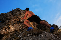 Free climber holding on the cliff. Muscular Climber climbs on a cliff with blue sky on background Royalty Free Stock Photography