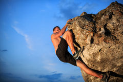 Free climber holding on the cliff. Muscular Climber climbs on a cliff with blue sky on background Royalty Free Stock Images