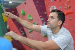 Free climber young man climbing artificial boulder in gym. Climber royalty free stock photos