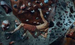 Free climber young man climbing artificial boulder indoors Royalty Free Stock Image