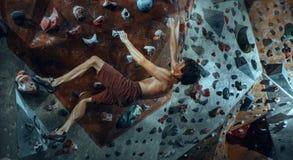 Free climber young man climbing artificial boulder indoors Royalty Free Stock Images