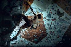 Free climber young man climbing artificial boulder indoors stock photography