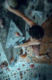 Free climber young man climbing artificial boulder indoors stock photo