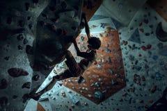 Free climber young man climbing artificial boulder indoors stock images