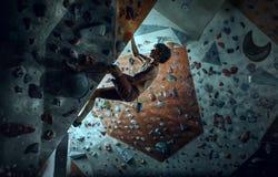 Free climber young man climbing artificial boulder indoors stock photos
