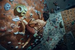 Free climber young man climbing artificial boulder indoors Royalty Free Stock Photo