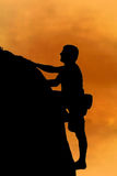 Free climbing. Silhouette of free style climber on top Royalty Free Stock Images